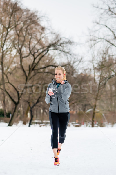 Stock photo: Woman running down a path on winter day in park