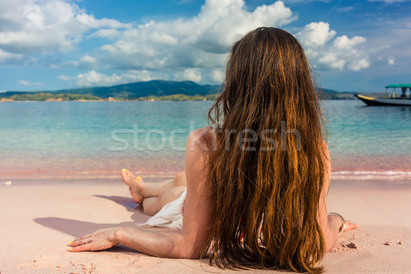 Young woman with long brown hair daydreaming while lying down on Stock photo © Kzenon