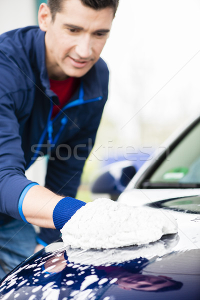 Hard-working man polishing car with white microfiber mitt Stock photo © Kzenon