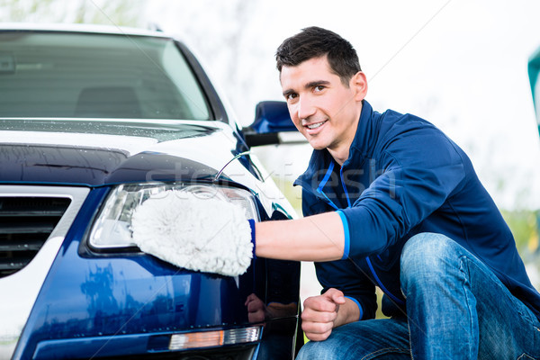 Smiling man cleaning the headlamp on his car Stock photo © Kzenon