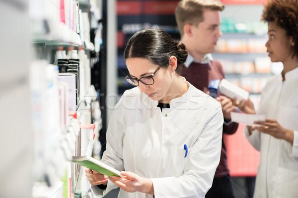 Portrait of a female experienced pharmacist reading indications Stock photo © Kzenon