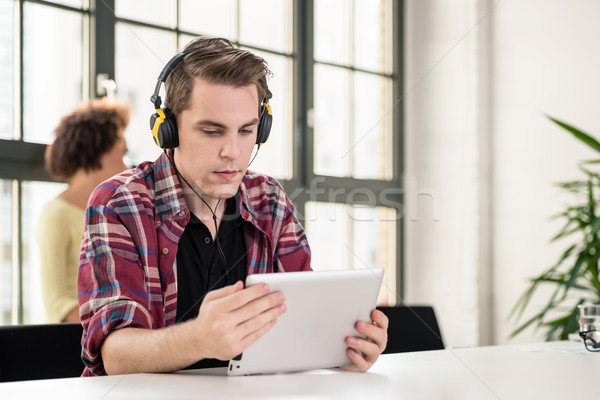 Young man watching a video on tablet PC at work Stock photo © Kzenon