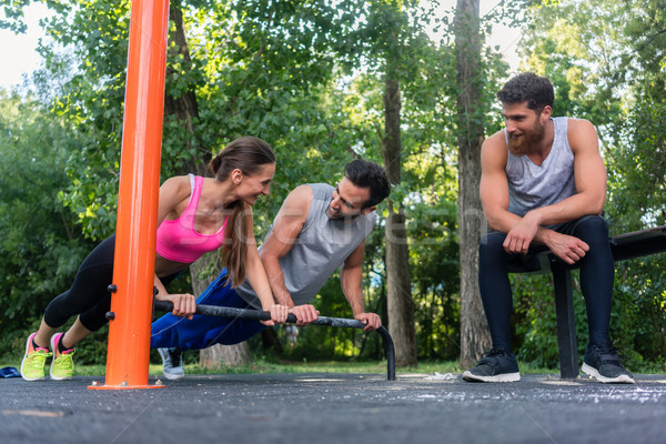 Young determined couple in love doing push-ups together in park Stock photo © Kzenon