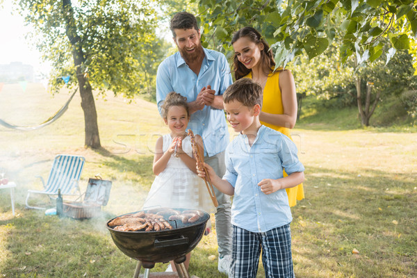 Portrait of happy family with two children standing outdoors near barbecue Stock photo © Kzenon