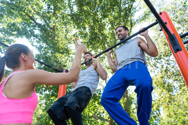 Two young men repeating pull-up exercise during upper-body routine Stock photo © Kzenon