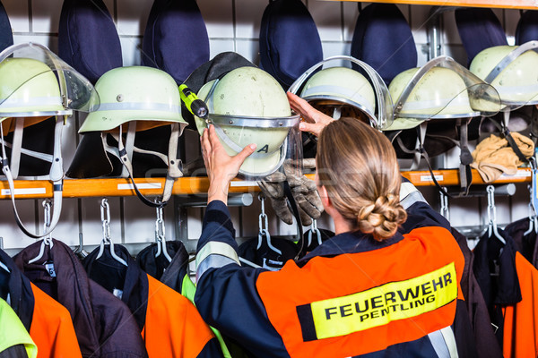 Female fire fighter in the locker room taking helmet Stock photo © Kzenon