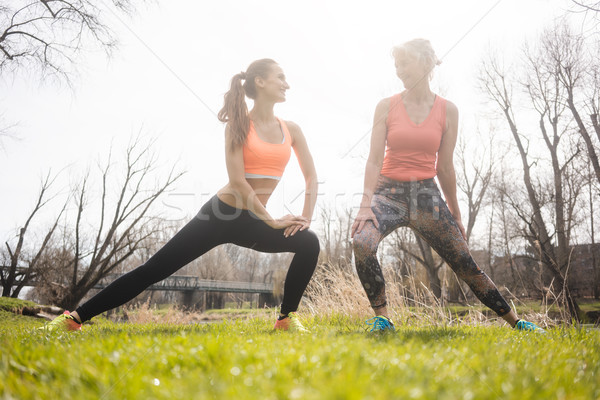 Mother and daughter stretching on meadow doing gymnastics Stock photo © Kzenon