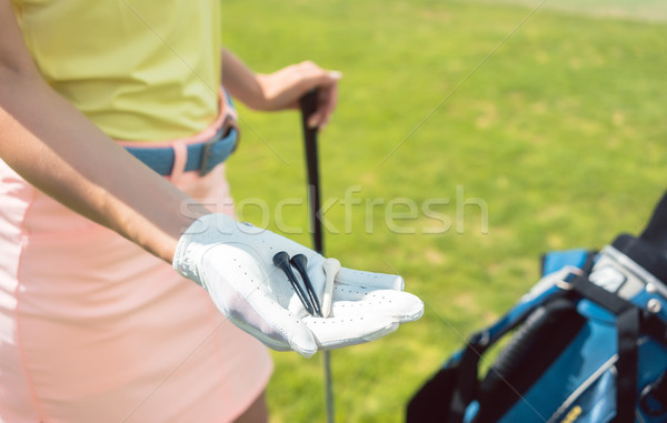 Close-up of the hand of a woman holding three tees on a golf course Stock photo © Kzenon