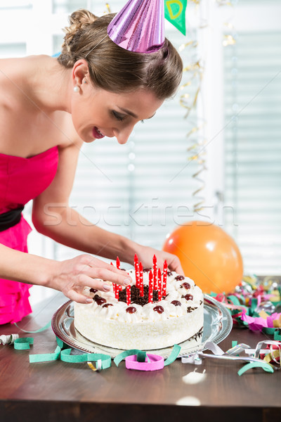 Portrait of a beautiful woman smiling while putting red candles on a cake Stock photo © Kzenon