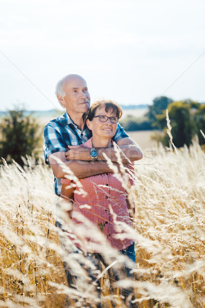 Senior man cuddling with his wife in the grass Stock photo © Kzenon