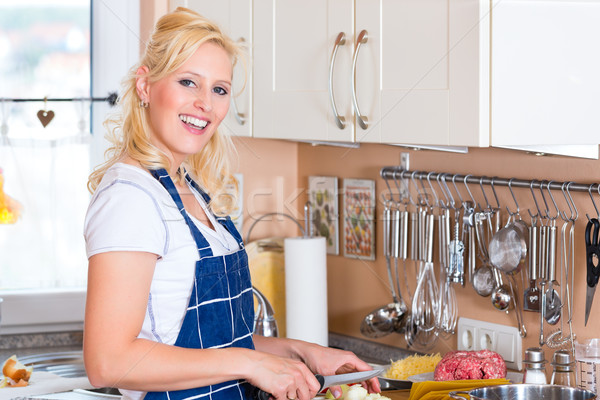 Young Housewife is cooking and chopping onions Stock photo © Kzenon