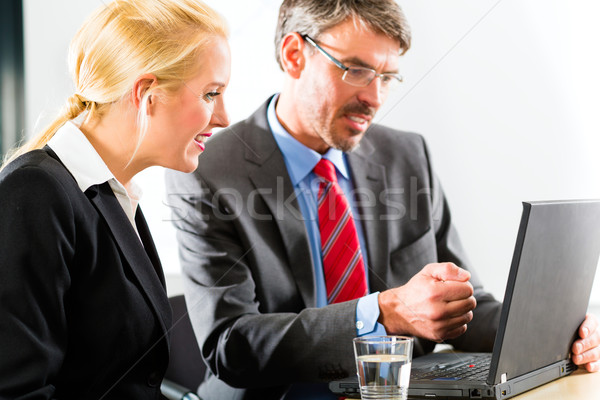 Businesspeople looking at laptop in consultation Stock photo © Kzenon