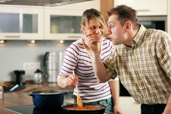 Cooking couple - tasting the sauce Stock photo © Kzenon