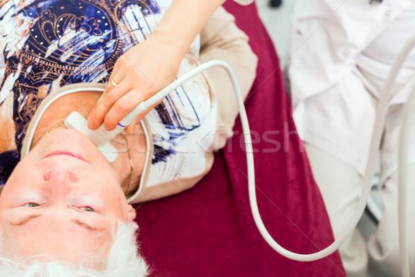 Doctor examining senior patient with ultrasonic Stock photo © Kzenon