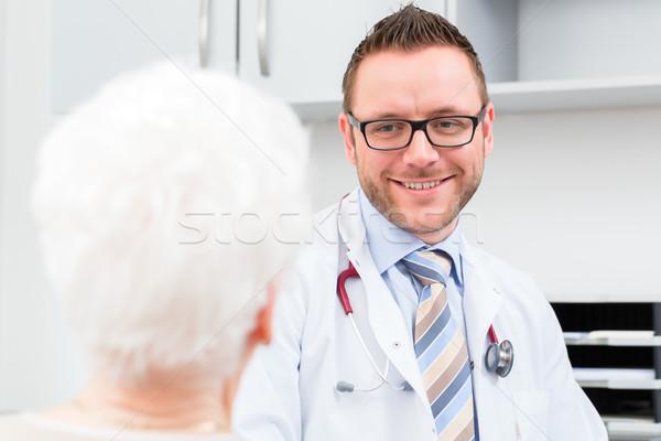 Doctor seeing senior patient in practice Stock photo © Kzenon