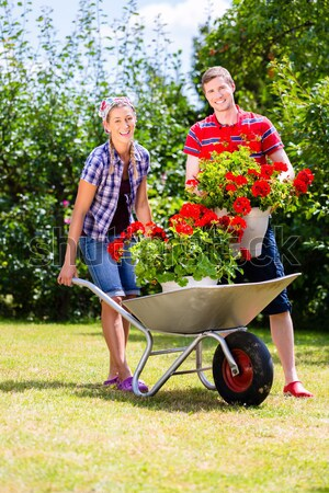 Couple in garden with watering can and barrow Stock photo © Kzenon