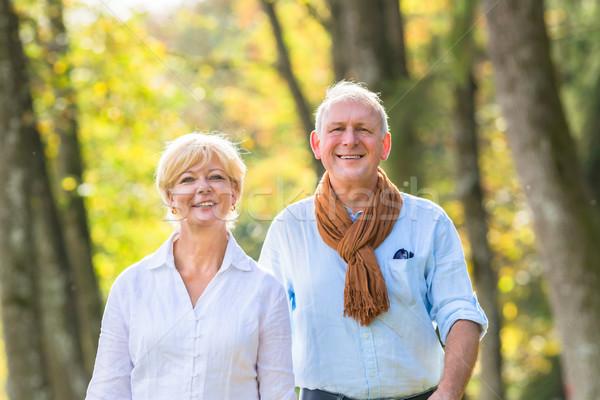 Senior couple having walk in wood  Stock photo © Kzenon