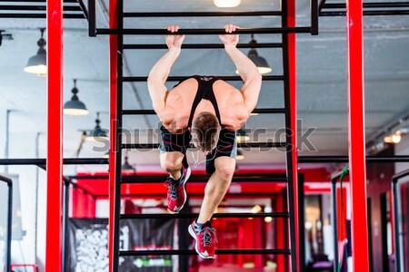 Man doing push-up in sport fitness gym Stock photo © Kzenon