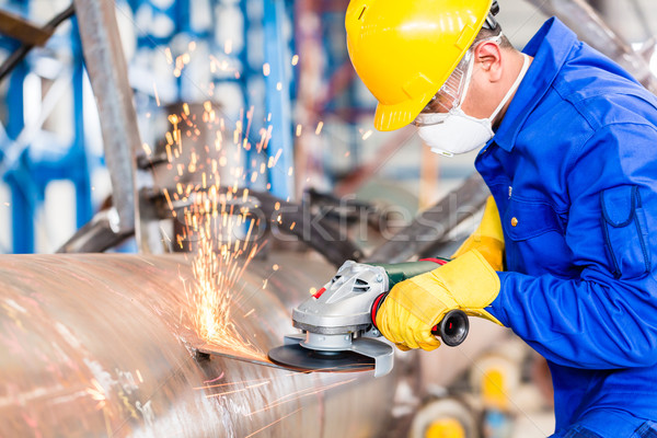 Metal worker in factory grinding metal of pipeline Stock photo © Kzenon