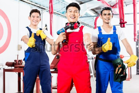 Three Asian industrial workers proud in factory Stock photo © Kzenon