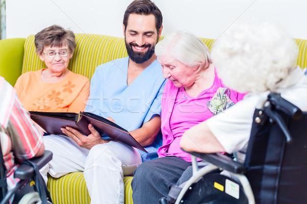 Geriatric nurse looking at pictures with seniors Stock photo © Kzenon