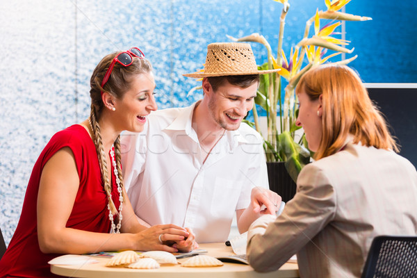 Couple in travel agency booking vacation trip Stock photo © Kzenon