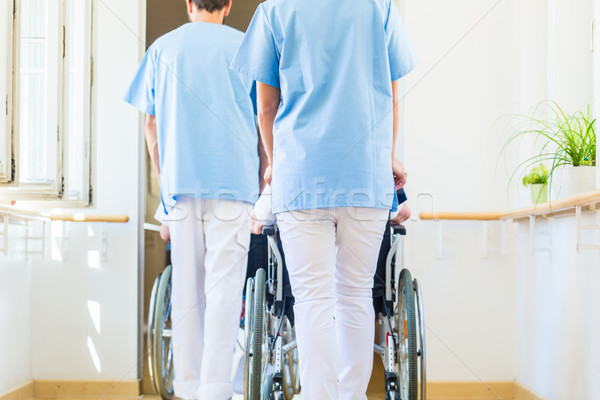 Nurses pushing seniors in wheelchair thru nursing home Stock photo © Kzenon