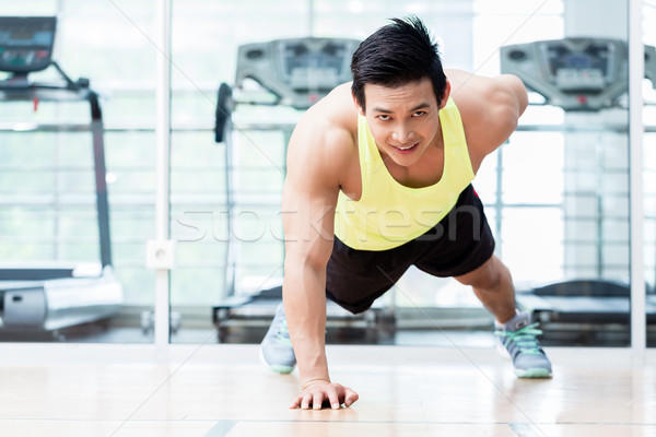Muscular young man doing one armed pushups in gym Stock photo © Kzenon