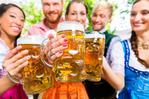 Friends in beer garden with beer glasses Stock photo © Kzenon