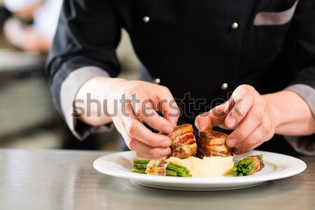 Chef finishing and garnishing food he prepared Stock photo © Kzenon