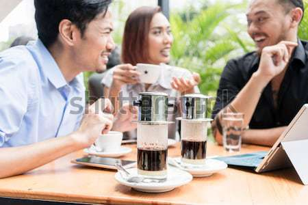 Vietnamese coffee served on the table of three friends outdoors  Stock photo © Kzenon