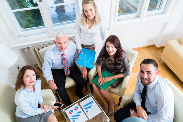 Five business people in team meeting studying graphs Stock photo © Kzenon