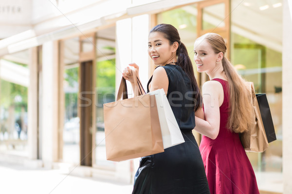 Stock photo: Two happy women looking at camera while carrying paper bags duri