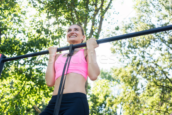 Cheerful young woman wearing pink sports bra while doing chin-up Stock photo © Kzenon