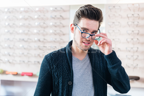 Man in front of shelf with glasses in optician shop Stock photo © Kzenon