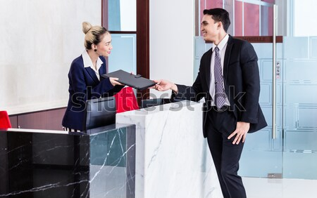 Manager and affiliate leaning at front desk of office  Stock photo © Kzenon