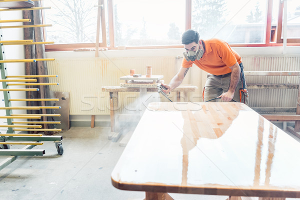carpenter man spraying varnish on a table he works on Stock photo © Kzenon