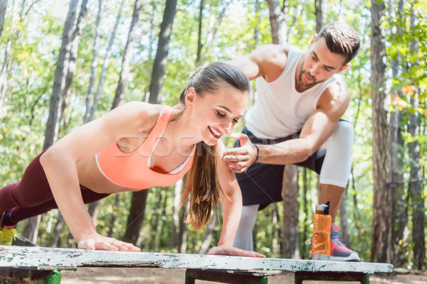 Sporty woman doing push-up in an outdoor gym Stock photo © Kzenon