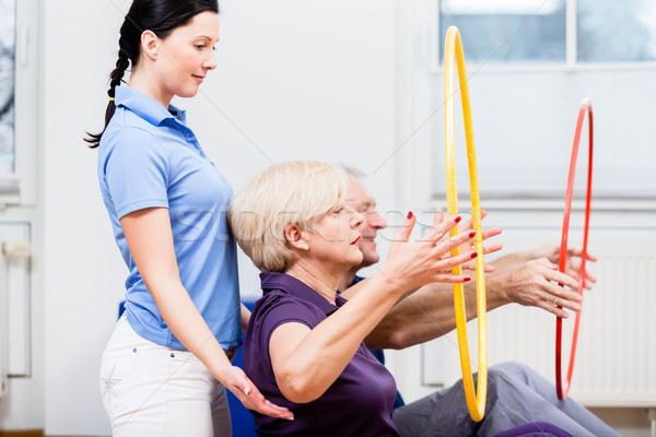 Senior couple in physiotherapy doing exercise with hula hoop Stock photo © Kzenon