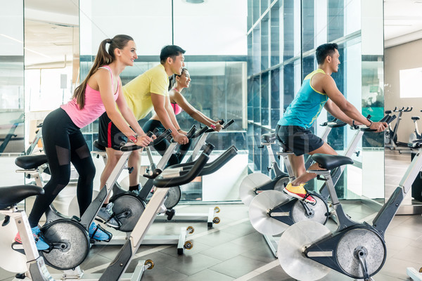 Stock photo: Fit women burning calories during indoor cycling class in the fitness club
