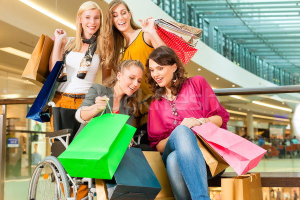 Négy női barátok pláza tolószék bevásárlótáskák Stock fotó © Kzenon