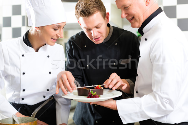Chef team in restaurant kitchen with dessert Stock photo © Kzenon