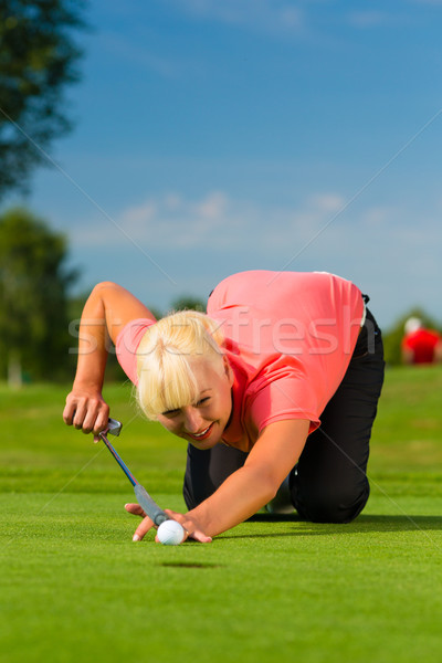 Young female golf player on course aiming for put Stock photo © Kzenon