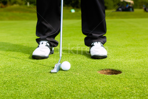 Stock photo: Golf player putting ball in hole