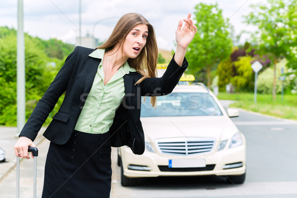 Young businesswoman calls for a taxi Stock photo © Kzenon