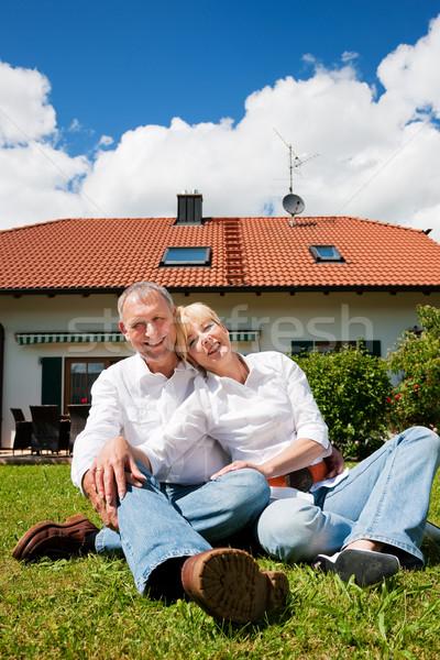 Starszy para posiedzenia domu słońce trawnik nowy dom Zdjęcia stock © Kzenon
