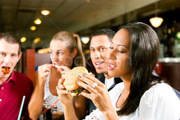 Stock photo: Friends eating fast food in a restaurant