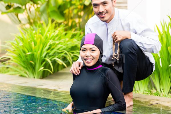Muslim woman in pool greeting her husband Stock photo © Kzenon