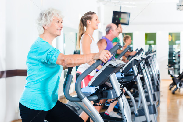 Group of people on elliptical trainer exercising in gym Stock photo © Kzenon