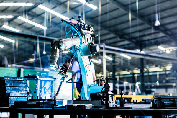 Welding robot in production plant or factory Stock photo © Kzenon